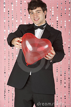Young Man Dressed In Suit Holding Heart