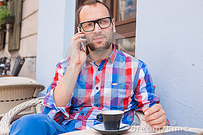 Young man drinking coffee in restaurant. He is holding a mobile phone.