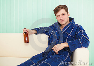 Young man drinks beer in dressing gown on sofa
