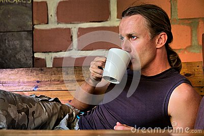 Young man drinks coffee lying next to fire