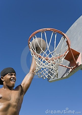 Young man dunking basketball into hoop