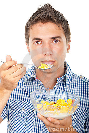 Young man eating cornflakes cereals