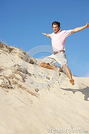 Young Man Enjoying Beach Holiday Running Down Dune