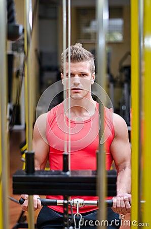 Young man exercising biceps on gym machine