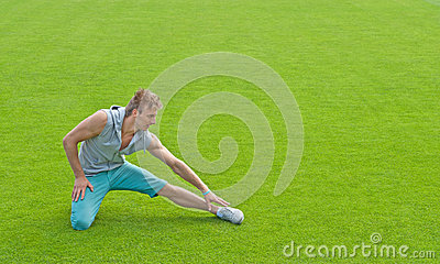 Young man exercising on sports field