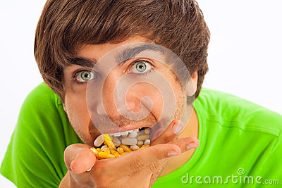 Young man feeding himself pills