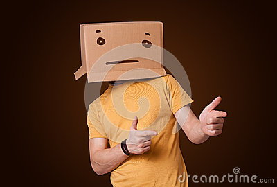 Young man gesturing with a cardboard box on his head with straig