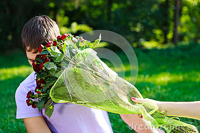 Young man gets hit in the face bouquet of red roses