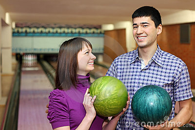 Young man and girl hold balls and laugh