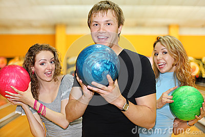 Young man and girls hold balls in bowling club