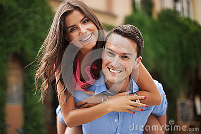 Young man giving his girlfriend a piggyback ride