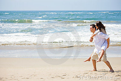 Young man giving piggyback to woman on beach