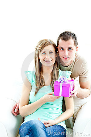 Young man giving present to his glowing girlfriend