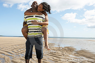 Young Man Giving Woman Piggyback Along Shoreline