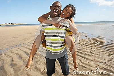 Young Man Giving Woman Piggyback Along Shoreline