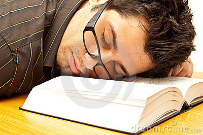 Young man with glasses fell asleep on a book