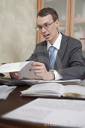Young man in glasses is looking at paper sheet