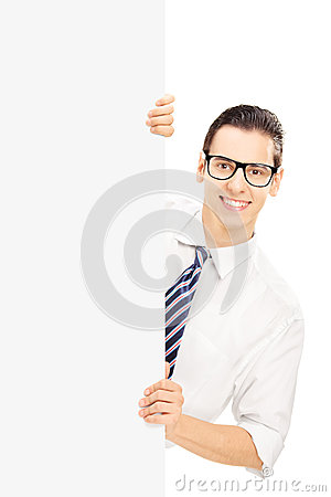 Young man with glasses posing behind a blank panel