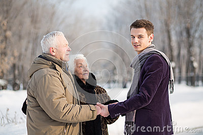 The young man greets an elderly couple in the park