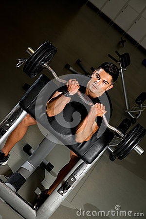 Young man in the gym exercising biceps with barbell