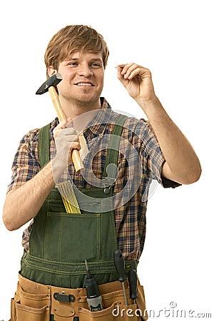 Young man hammering nail