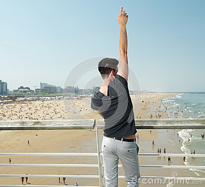 Young man with hand raised pointing up, beach in background