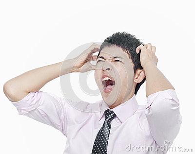 Young man with hands on head screaming
