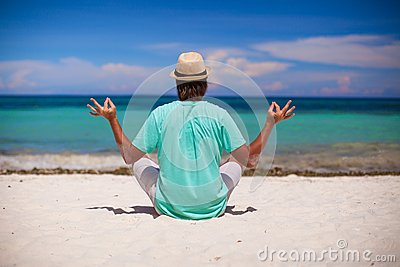Young man in hat sitting in the lotus position on