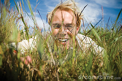 Young man hiding in the grass