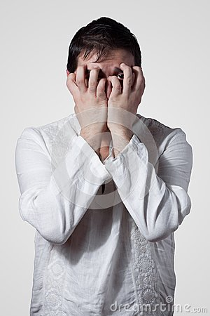Young man hiding his face with hands