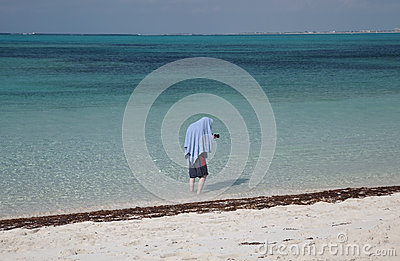 Young man hiding from the sun under a towel