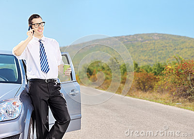 Young man on his automobile drinking coffee and talking on a pho