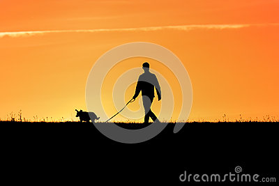 Young man with his dog - back lit