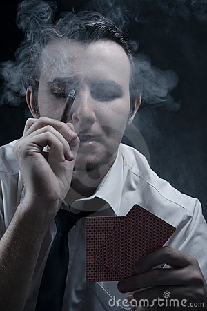 Young man holding cards and cigar in smoke