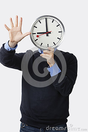 Young man holding clock over his face gesturing against white background