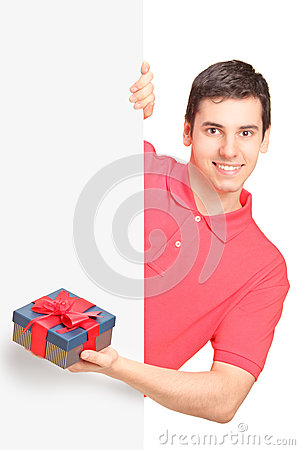 Young man holding a gift and standing behind panel
