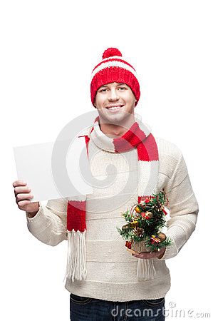 Young man holding small christmas tree and sign
