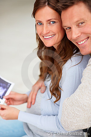 Young man holding sonogram and embracing his wife
