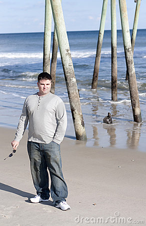 Young Man Holding Sunglasses at the Beach