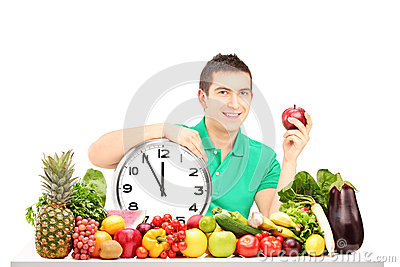 Young man holding a wall clock and apple, sitting on a table ful