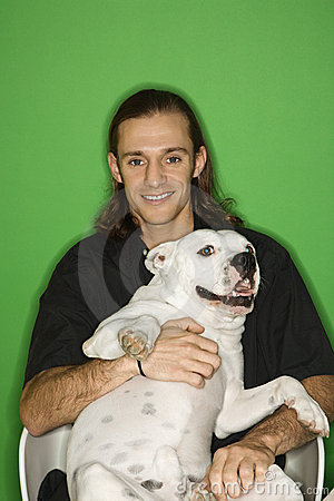 Young man holding white dog on lap.