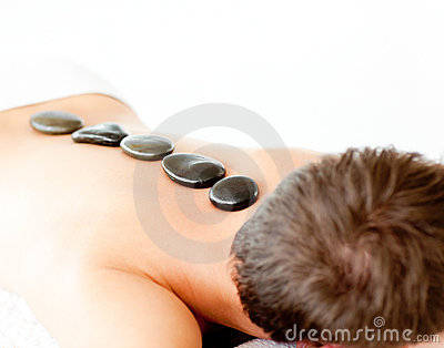Young man with hot stones in a spa center