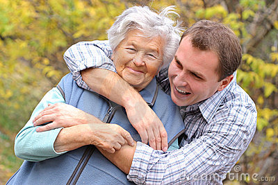 Young man hugs elderly woman