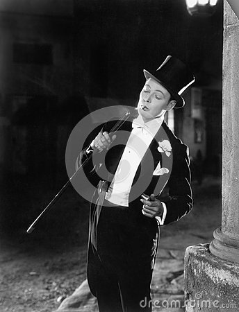 Free Young Man In Formal Clothing Lighting His Cigarette With His Walking Stick Royalty Free Stock Photos - 52021138