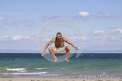 Young man jumping against blue sky and sea.