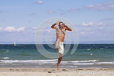 Young man jumping on the blue beach.