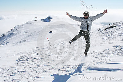 Young man jumping for fun in the snow