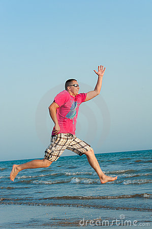 Young man jumping in the ocean