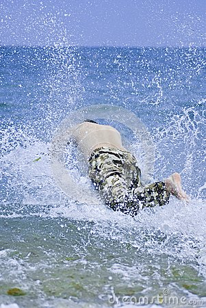 Young man jumping into sea water