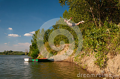 Young man jumping from the shore into the river